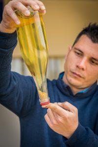 Il produttore Diego con una bottiglia di vino bianco in mano Colli Euganei